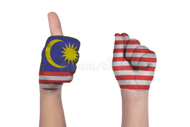 Händer för barn` som s visar gest sextio med den målade Malaysia flaggan royaltyfria foton