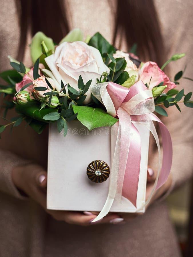 Händer för blomsterhandlare för affärskvinna som rymmer moderiktig bukettsammansättning i ask i blomsterhandel arkivfoton
