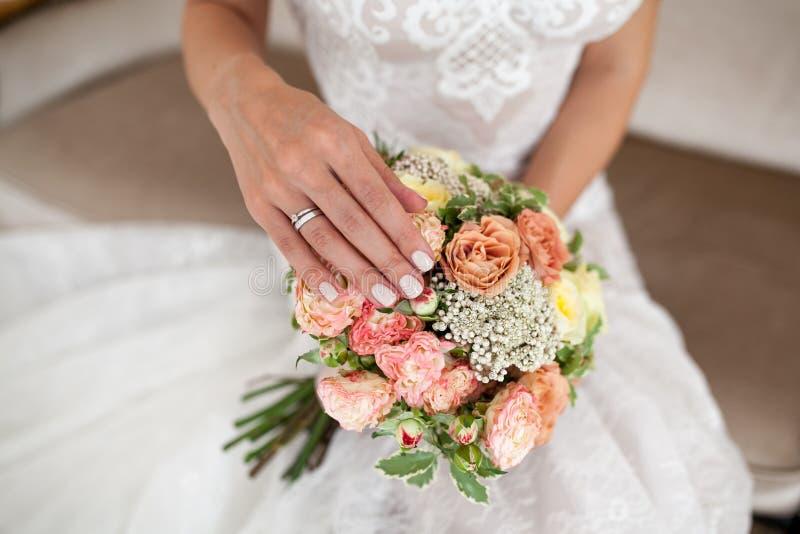 Händer för brud` s med beige manikyr på bröllopbukett Närbild arkivbilder