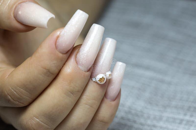 Händer för brud` s med enkel manikyr med lite juveln på naen royaltyfri foto