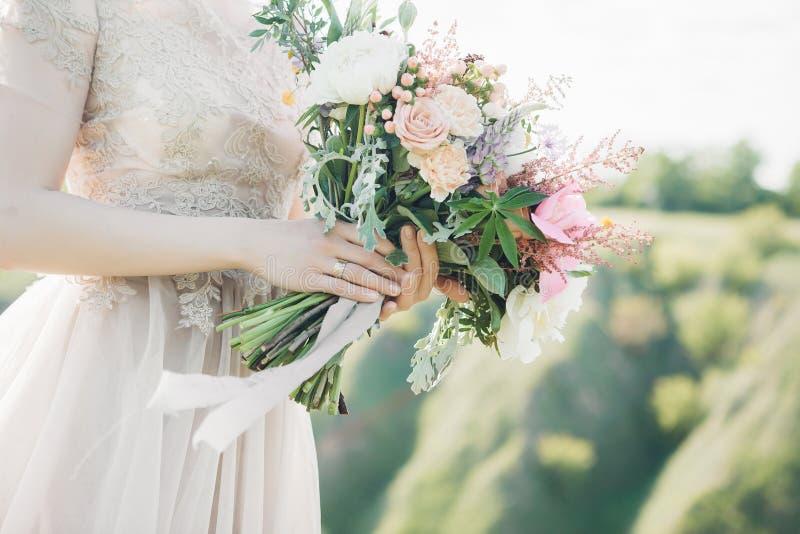 Händer för brud` s rymmer den härliga brud- buketten av pionen Konstfotografi royaltyfri foto