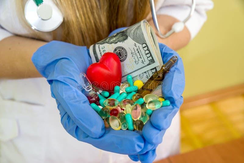 Händer för doktors` s rymmer den isolerade dollaren och olika preventivpillerar royaltyfri bild