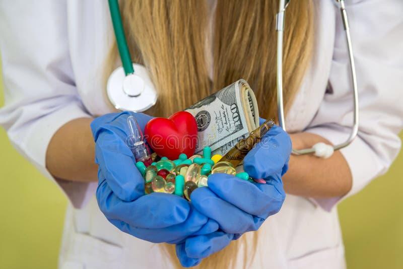 Händer för doktors` s rymmer dollaren och olika preventivpillerar som isoleras på gräsplan arkivfoto