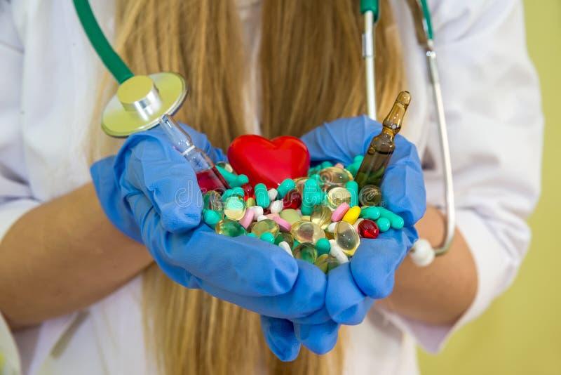 Händer för doktors` s rymmer olika preventivpillerar isolerade arkivbild