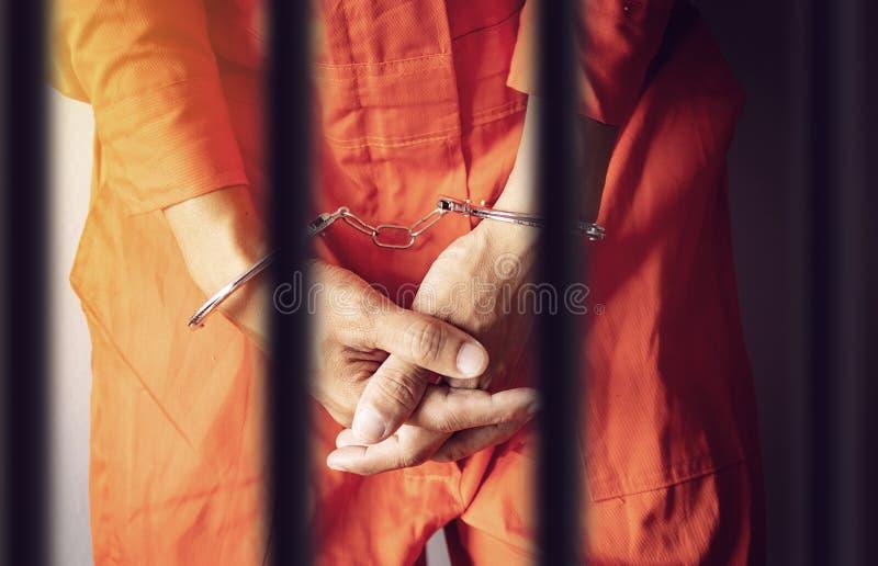 Händer för en fånge i handbojor bak stängerna av ett fängelse i orange jumpsuitkläder arkivbild