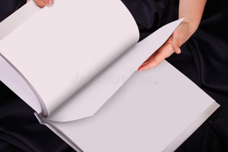 Händer för en kvinna två rymmer en tom bokspridning arkivbild