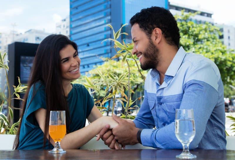 Händer för förälskelseparinnehav i en restaurang royaltyfria bilder