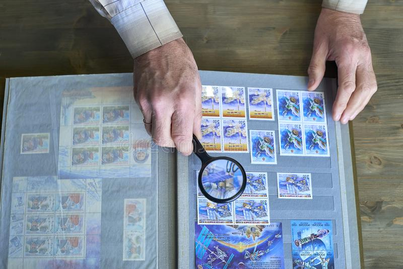 Händer för hög man rymmer förstoringsapparat- och stämpelalbumet med portostämpelsamlingen, utrymmetemat, träbakgrund arkivbilder