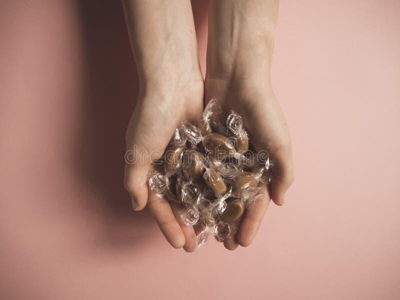 Händer för karamellgodisar itu arkivfoto