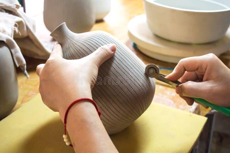 Händer för keramiker` s gör en dekorativ modell på vasen arkivbilder
