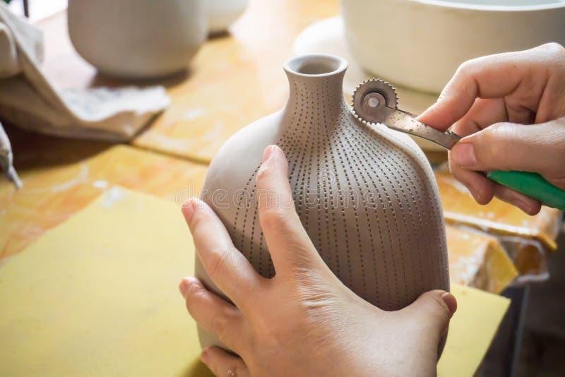 Händer för keramiker` s gör en dekorativ modell på vasen arkivfoto