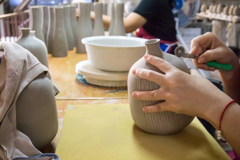 Händer för keramiker` s gör en dekorativ modell på vasen fotografering för bildbyråer
