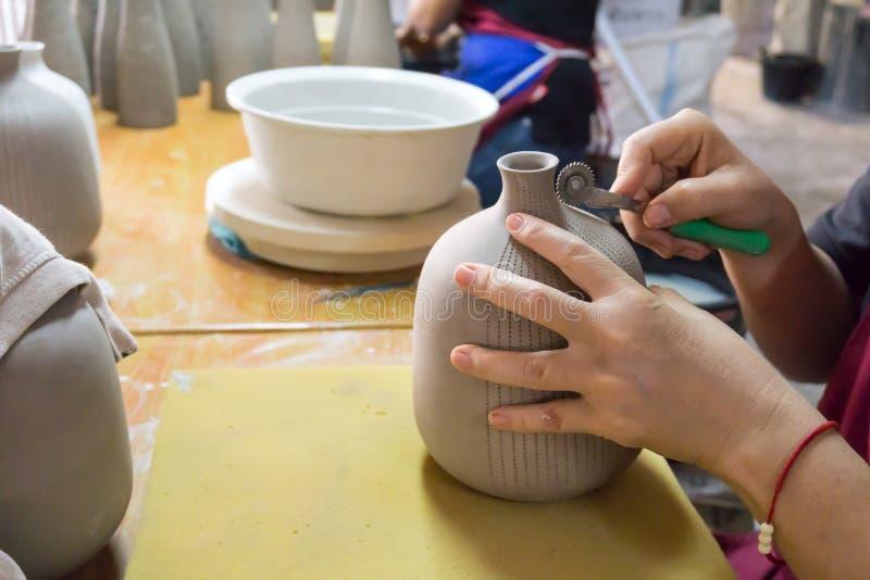 Händer för keramiker` s gör en dekorativ modell på vasen royaltyfri foto