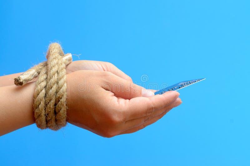 Händer för kvinna` s band med ett rep och ett innehav en kreditkort Krediteringsträldom arkivbild