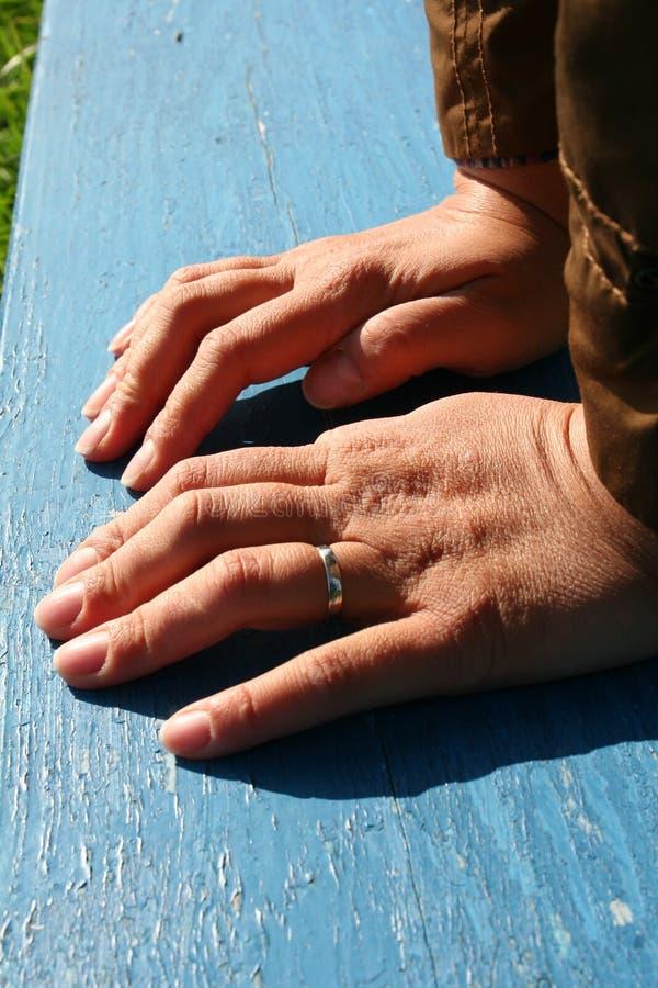 Händer för kvinna` s baseras på en bänk royaltyfri foto