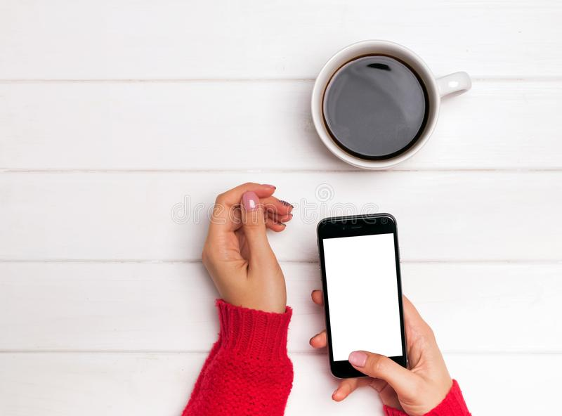 Händer för kvinna` s i hållande smartphone för röd tröja med tom vit royaltyfria foton