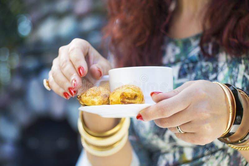 Händer för kvinna` s med guld- armband, cirklar, koppen kaffe och a royaltyfri foto