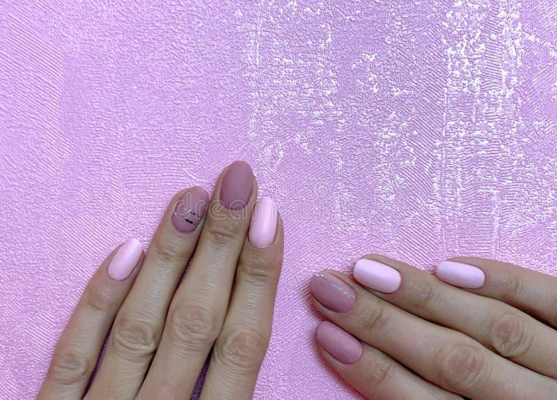 Händer för kvinna` s med perfekt näck manikyr Spika polermedel är en naturlig gräns - rosa skugga Närbild på rosa bakgrund arkivfoton