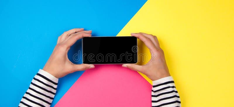 Händer för kvinna` s med smartphonen på färgrik bakgrund royaltyfria bilder