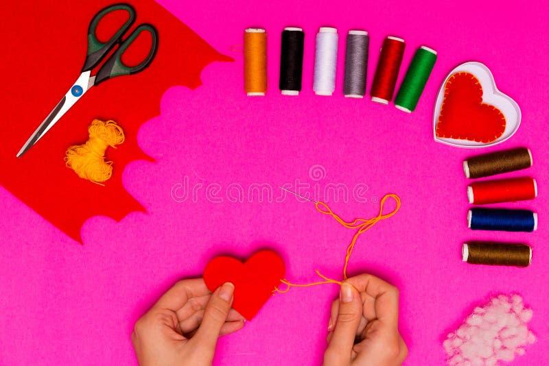 Händer för kvinna` s syr en kudde i form av en hjärta på en rosa tabell Valentinbakgrund med handgjorda sydde kuddehjärtor i kvin fotografering för bildbyråer