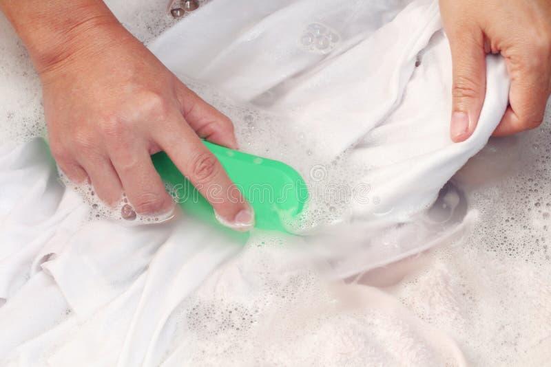 Händer för kvinna` som s tvättar vit färgkläder i handfatet royaltyfri foto