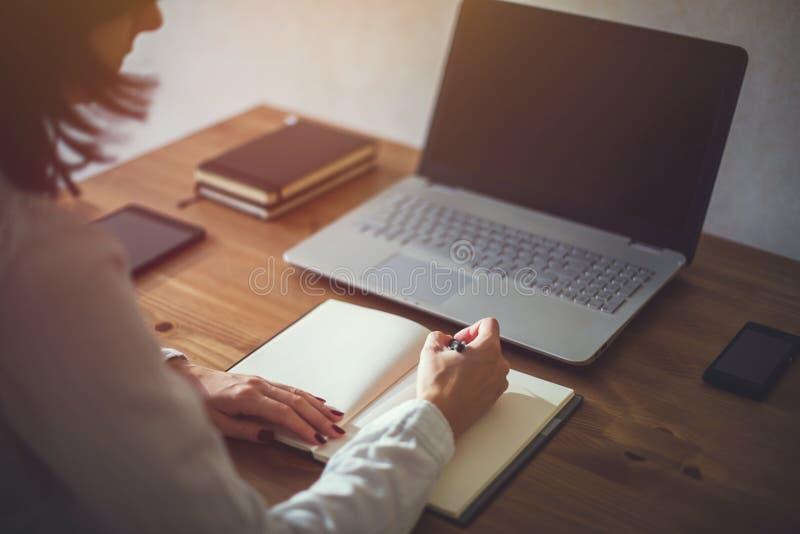 Händer för kvinnafreelancerkvinnlig med pennhandstil på anteckningsboken hemma eller kontor arkivfoton