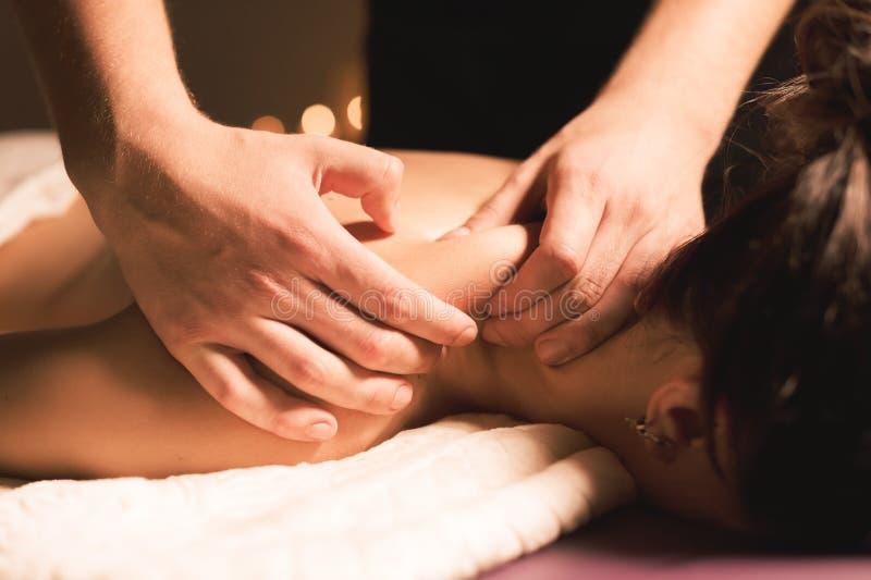 Händer för man` s gör en terapeutisk halsmassage för en flicka som ligger på en massagesoffa i en massagebrunnsort med mörk belys arkivbilder