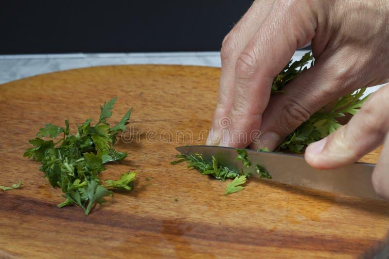 Händer för man` s klippte persilja med en kniv på en skärbräda royaltyfria bilder
