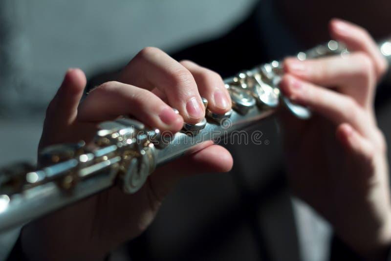 Händer för man` s på ett vindmusikinstrument leka för flöjt grunt djupfält Musik och ljud Modellera ljus fotografering för bildbyråer