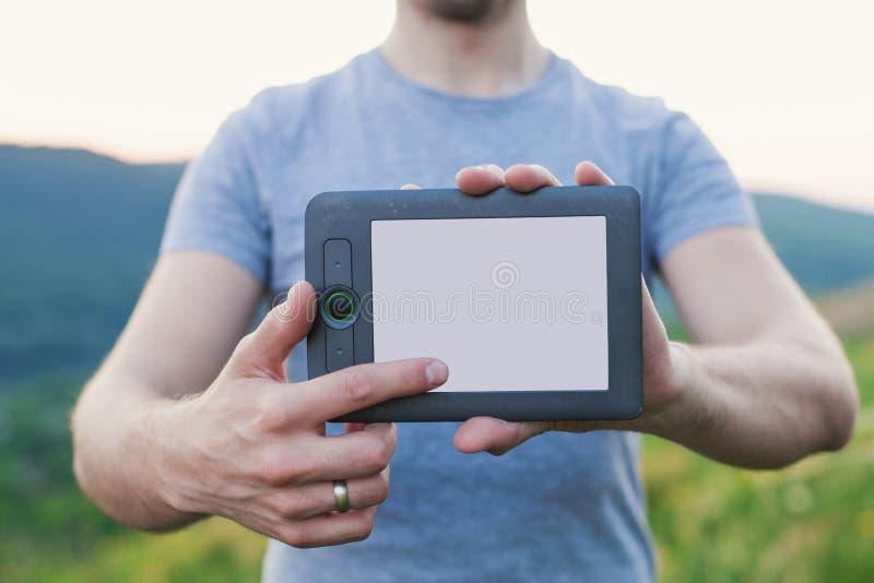Händer för man` s rymmer den elektroniska boken och handlag skärmen royaltyfri fotografi