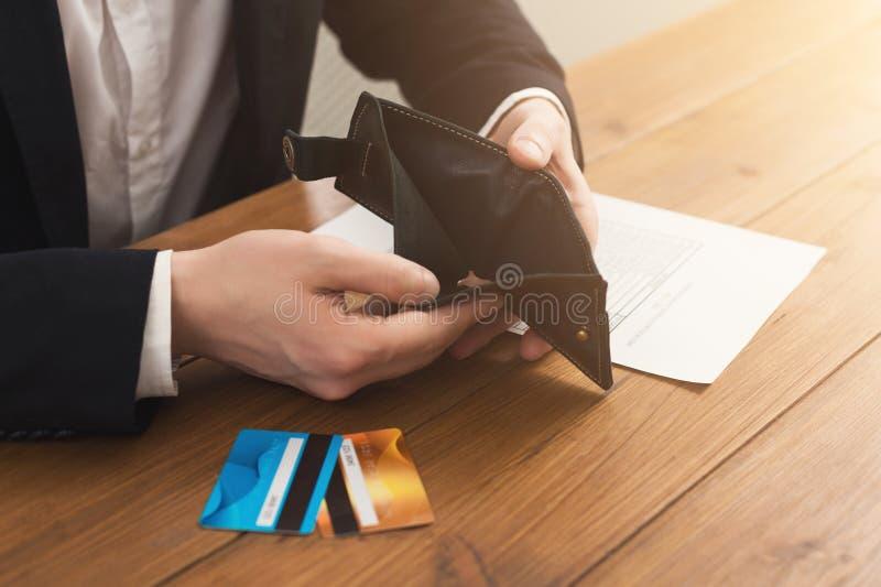 Händer för man` som s rymmer den öppna tomma plånboken arkivbild
