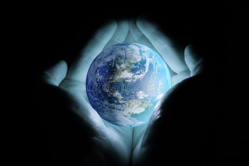 Händer för man` som s rymmer planetjorden med ett blått glöd på en svart bakgrund royaltyfri bild