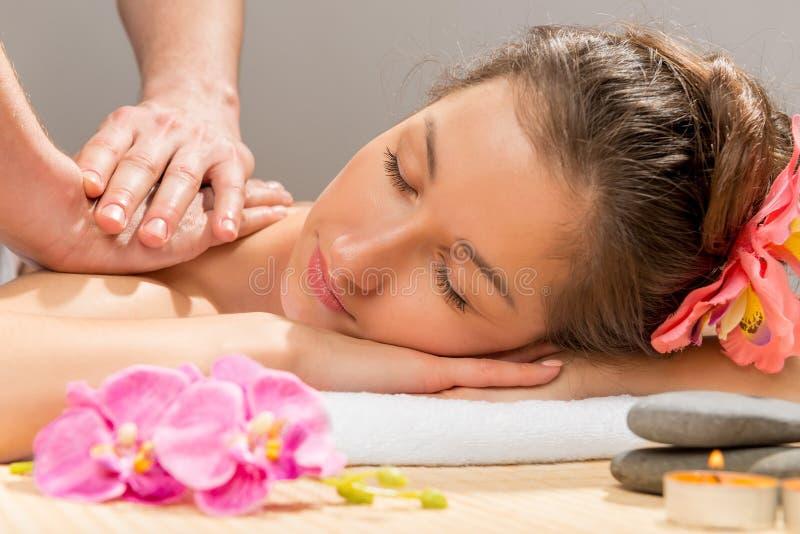Händer för massör` som s gör massageskuldran arkivbild