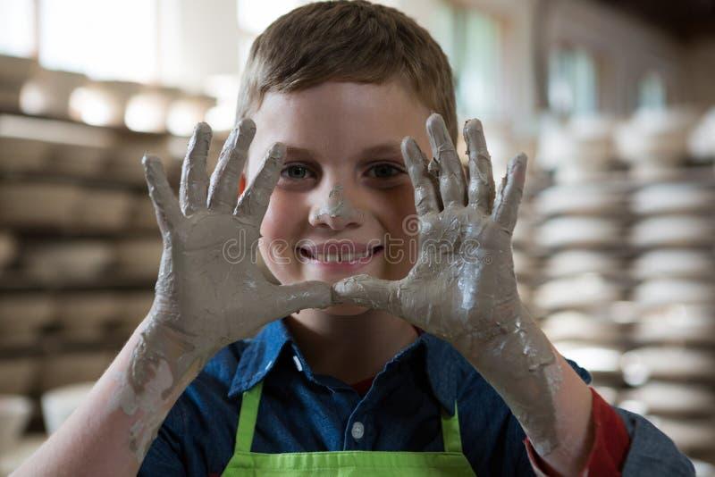 Händer för pojkevisninglera i krukmakeri shoppar arkivfoton