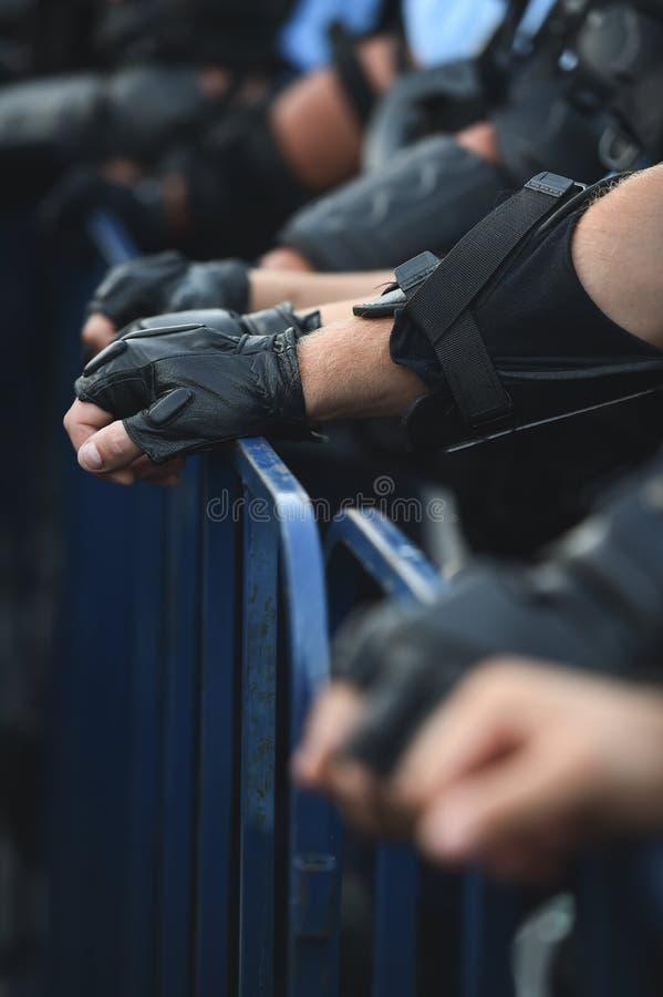 Händer för säkerhetspersonal på ett skydd fäktar under en tumult arkivfoton