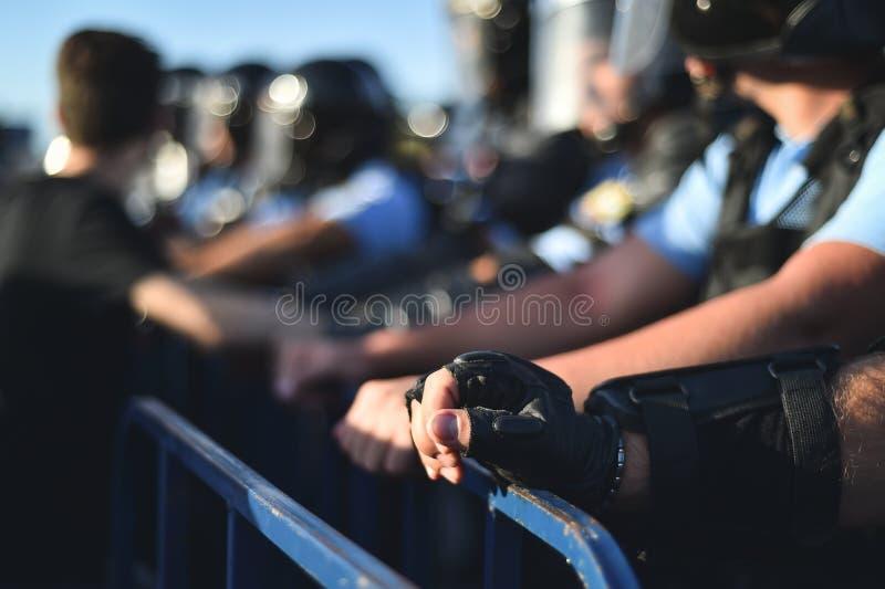 Händer för säkerhetspersonal på ett skydd fäktar under en tumult arkivbilder