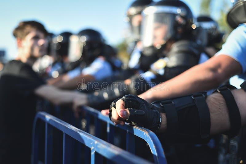 Händer för säkerhetspersonal på ett skydd fäktar under en tumult arkivbild