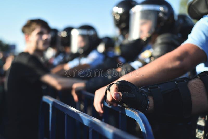 Händer för säkerhetspersonal på ett skydd fäktar under en tumult arkivfoto