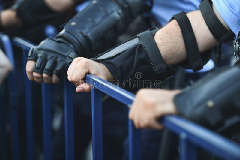 Händer för säkerhetspersonal på ett skydd fäktar under en tumult royaltyfria foton