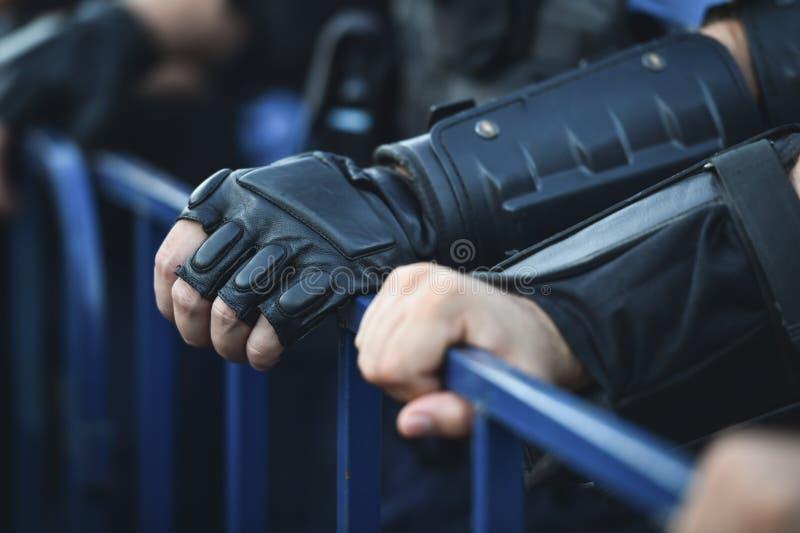 Händer för säkerhetspersonal på ett skydd fäktar under en tumult fotografering för bildbyråer