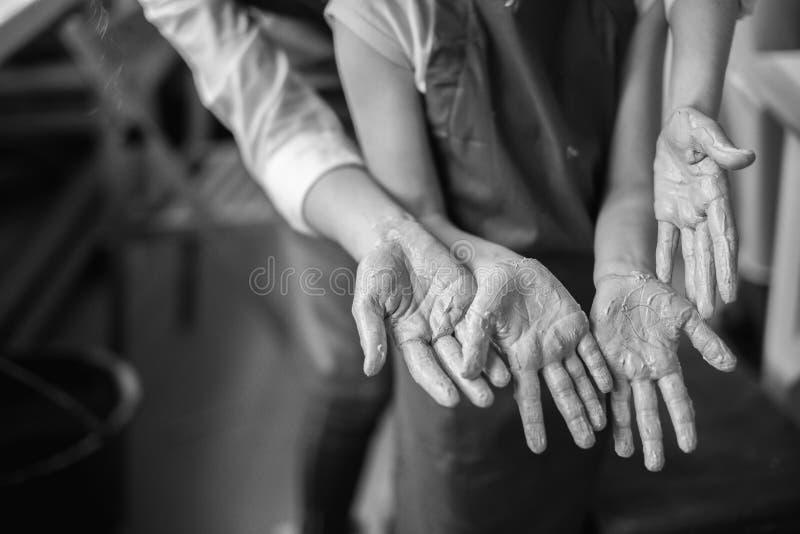 Händer för ` s för händer och för barn för keramiker` s i lera fotografering för bildbyråer