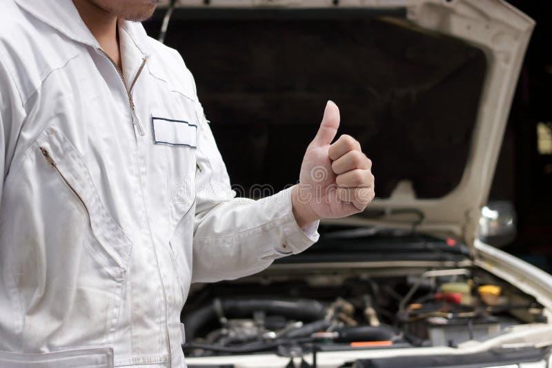 Händer för slut upp av den yrkesmässiga unga mekanikern man upp visningtummen som tecken av framgång med bilen i öppen huv på gar arkivfoto