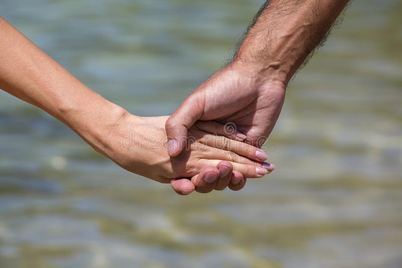 Händer för sommarparinnehav på stranden Det romantiska barn kopplar ihop att tycka om sunen, solsken, roman och förälskelse vid h arkivfoto