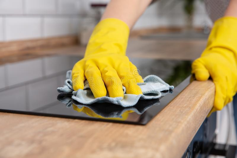 Händer för ung kvinna som gör ren en modern svart induktionshob förbi en trasa, hushållsarbete royaltyfria foton