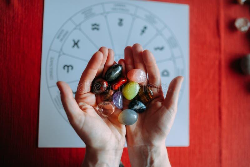 Händer för ung kvinna som visar gruppen av färgrika kristallstenar under tarokläsning med röd bakgrund royaltyfri bild