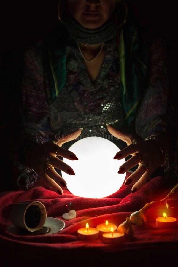 Händer från zigensk förmögenhetkassör ovanför magikristallkula royaltyfria foton