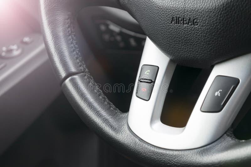 Händer frigör knappar på styrningen rullar in svart läder, moderna bilinredetaljer Mjuk belysning Abstrakt begrepp beskådar royaltyfria foton