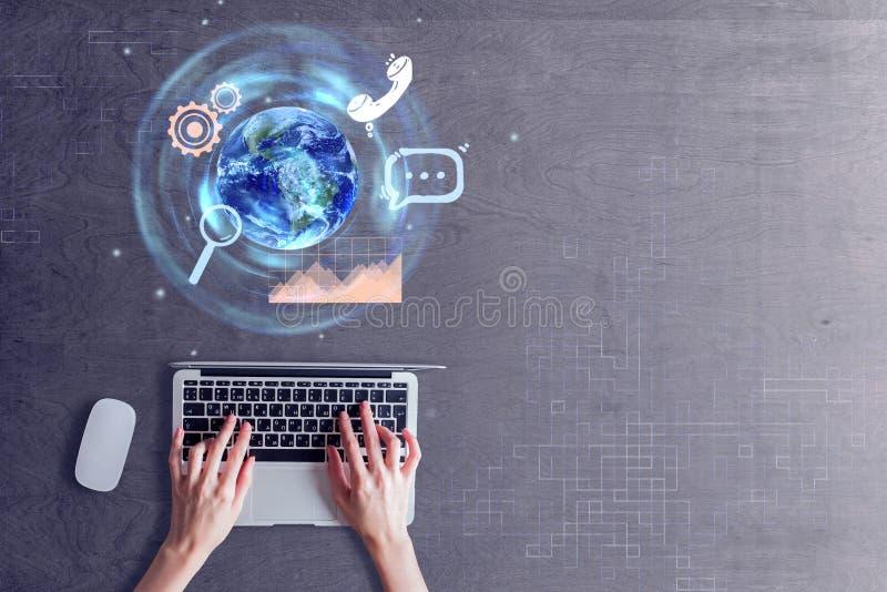 Händer genom att använda bärbara datorn med jordklotet arkivfoto