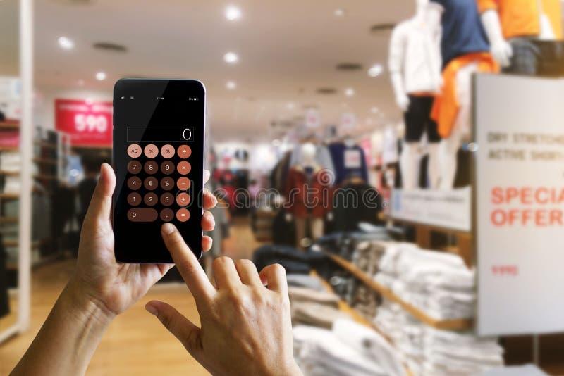 Händer genom att använda räknemaskinapplikation på den mobila smartphonen royaltyfria bilder