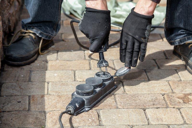 Händer i arbetshandskar sätter in den elektriska proppen in i håligheten royaltyfri fotografi